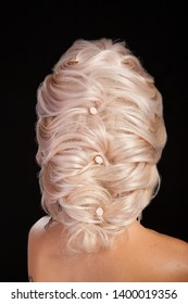 High end fashion coiffure on young woman with blonde hair. Female elegance. Modern hair style.