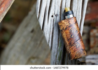 high end natural stabilized wood regulated box mods with rebuildable dripping atomizer and ultem drip tip, vaping device, selective focus