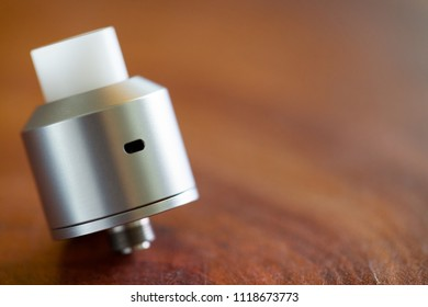 high end rebuildable dripping atomizer in simple design with white delrin drip tip on the wood texture background, vape gear, vaporizer equipment, selective focus with shallow depth of field