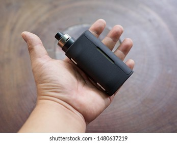 high end rebuildable dripping atomizer with black regulated box mods in hand on natural wood texture background, vaping device, selective focus with shallow depth of field