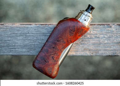 high end rebuildable dripping atomizer with stabilized natural redwood burl regulated box mods on an old wood texture background, vaping device, selective focus