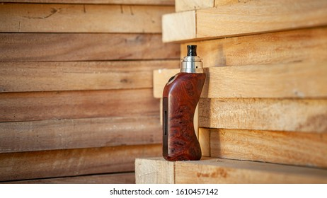 high end rebuildable dripping atomizer with stabilized natural redwood burl regulated box mods on natural wood texture background, vaping device, selective focus