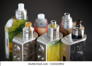 high end rebuildable dripping atomizers for flavour chaser on regulated stabilized wood box mods, vaping device, vape gear, vaporizer equipment, selective focus with shallow depth of field