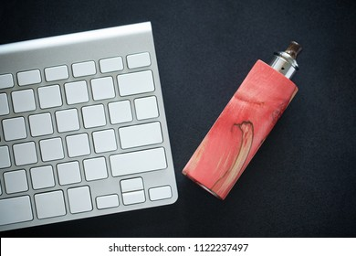high end red and natural spalted stabilized wood box mods with rebuildable dripping atomizer beside wireless keyboard on dark grey texture background, vape, vaping device, selective focus