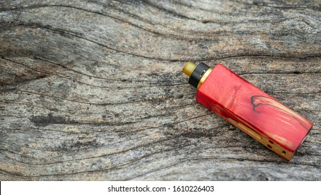 high end red natural stabilized wood regulated box mods with rebuildable dripping atomizer on natural timber wood texture background, vaporizer equipment, selective focus
