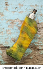 high end yellow green stabilized poplar burl wood box mods with rebuildable dripping atomizer and drip tip vape gear on old wood texture background, vaporizer equipment, selective focus