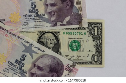 High exchange rate between American Dollar and Turkish lira.One dollar is five Turkish lira on August/2018.A dollar between two five lira,on the white ground.