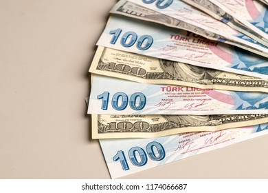 High exchange rate between American Dollar and Turkish lira.one hundred  dollar is seven hundred Turkish lira.One dolar and seven liras in like steps,on the white surface.