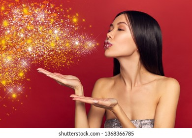 High Fashion Beauty Model Girl blowing Sparkling Glitter shine. Red sparkle Lipstick and perfect make-up. Vogue Style Portrait, girl touching her cheeks