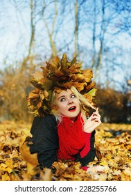 High fashion blonde girl with the red lips in the wreath of leaves and in the fallen leaves in the park outdoor - Shutterstock ID 228255766