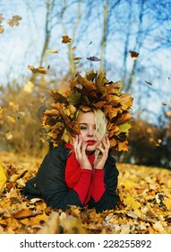 High fashion blonde girl with the red lips in the wreath of leaves and in the fallen leaves in the park outdoor - Shutterstock ID 228255892
