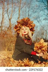 High fashion blonde girl with the red lips in the wreath of leaves and in the fallen leaves in the park outdoor - Shutterstock ID 229176322