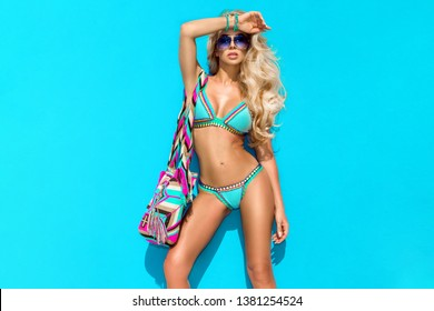 High fashion colors,Glamour Portrait of pretty beautiful fashion woman in bikini posing in summer near the sea and blue sky in sunshine with gorgeous sunglasses,tropic island girl on vacation - Image
