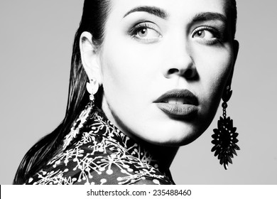 High fashion concept. Portrait of glamorous young model with long wet hair, luxurious earrings and perfect make-up posing over gray background. Deep shadows. Vogue style. Close up. Studio shot