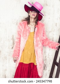 High fashion girl posing near the stair in studio in hat and pink fur coat
