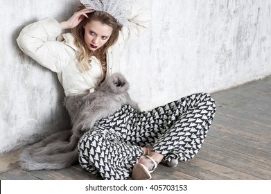 High fashion girl  sitting at the wall on the wood floor  in trousers  and  fur coat