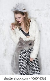 High fashion girl standing  at the white  wall  in trousers and fur coat