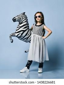 High fashion little asian girl kid in modern dress and sunglasses posing with zebra metallic balloons for kids birthday