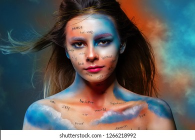 High fashion look of a beautiful stylish woman with bright makeup, written words on her face. Beautiful model with creative make-up. face close up