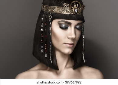 High fashion look. Glamorous closeup portrait of beautiful sexy stylish brunette young woman model with bright  makeup with perfect clean skin with gold jewelery. Cleopatra