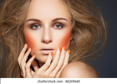 High fashion look. Woman model with fashionable makeup, bright orange blusher, manicure and big hairstyle