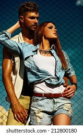 High fashion look.beautiful couple sexy stylish blond young woman model with bright makeup with perfect sunbathed skin and handsome muscled man in vogue style in jeans outdoors behind blue sky