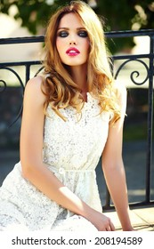 High fashion look.glamor closeup portrait of beautiful sexy stylish blond young woman model with bright makeup and pink lips with perfect clean skin in white summer dress in the city