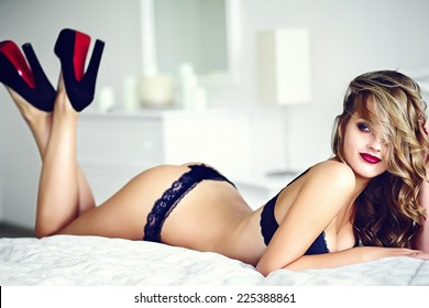 High fashion look.glamor closeup portrait of beautiful sexy stylish  young woman model lying on white bed with bright makeup, with red lips,  with perfect clean skin in black lingerie on bed