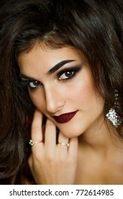 High fashion Look.glamor closeup portrait of beautiful sexy stylish Caucasian young woman model brunette with large earrings and bright makeup , with perfect clean skin