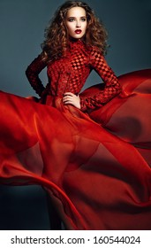 High fashion look.glamor portrait of beautiful sexy stylish brunette Caucasian young woman model with bright makeup, with healthy curly hair in bright red flying dress in studio