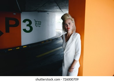 High fashion look.glamor portrait of beautiful sexy stylish Caucasian young woman model in a car parking. woman dressed in white elegant suit