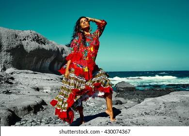 High fashion look.glamor sexy Caucasian model girl in black swimweari posing behind blue beach ocean water in vogue style in sunglasses