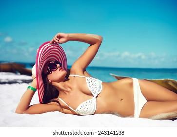 High fashion look.glamor sexy sunbathed model girl in white lingerie bikini in colorful sunhat behind blue beach ocean water