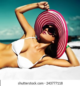 High fashion look.glamor sexy sunbathed model girl in white lingerie bikini in colorful sunhat behind blue beach ocean water in vogue style