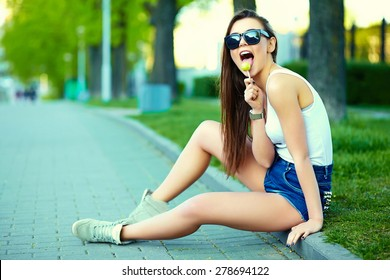 High fashion look.glamor stylish sexy smiling beautiful young woman model in summer bright hipster cloth in the street  with sweet lollipop