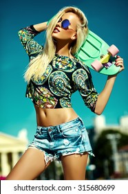 High fashion look.glamor stylish sexy beautiful young blond  model girl in summer bright casual hipster clothes with skateboard behind blue sky