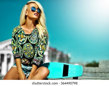 High fashion look.glamor stylish sexy beautiful young cute blond model girl in summer bright casual hipster clothes with skateboard sitting behind blue sky