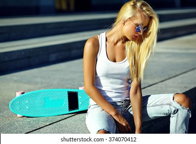 High fashion look.glamor stylish sexy beautiful young cute blond model girl in summer bright casual hipster clothes with skateboard
