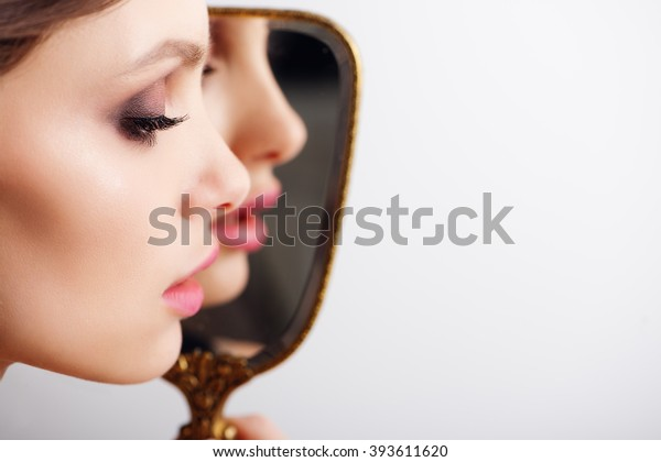 High fashion look.glamour fashion portrait of beautiful sexy brunette girl female model with bright makeup and red lips and her reflection in mirror with perfect skin