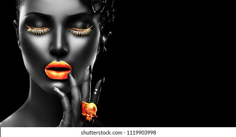 High Fashion Model with black skin, gold lips, eyelashes and jewellery - golden ring on hand. Isolated on black background. Beauty Woman face, beautiful make-up. Gorgeous lady fashion art portrait.