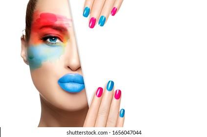 Modelo de alta moda con maquillaje de ojos de color, piel perfecta, labios brillantes azules y uñas coloridas, mitad cara con una plantilla de tarjeta blanca. Concepto de publicidad de moda para maquillaje y cosméticos