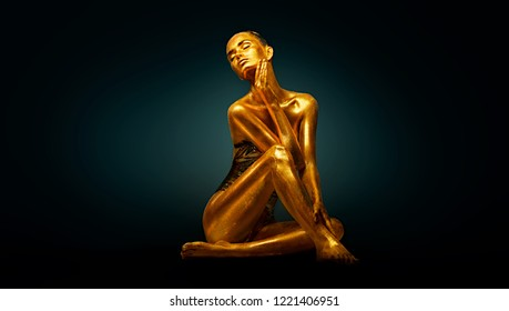 High Fashion model girl with bright golden sparkles on her body posing, full length portrait of beautiful sexy woman with glowing body skin. Art design make up. Glitter gold sequins on skin body art