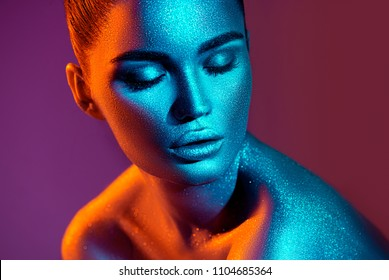 High Fashion model girl in colorful bright sparkles and neon lights posing in studio, portrait of beautiful sexy woman, trendy glowing make-up. Art design colorful make up. Glitter Vivid neon makeup