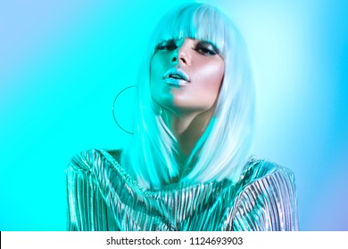 High Fashion model girl in colorful bright neon lights posing in studio, portrait of beautiful woman in white wig and silver trendy glowing make-up. White hair, colorful make up. Glitter neon makeup