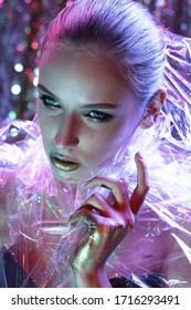 High Fashion model girl in colorful bright neon lights posing in studio through transparent film. Portrait of beautiful sexy woman in UV. Art design colorful make up. On colourful vivid background.