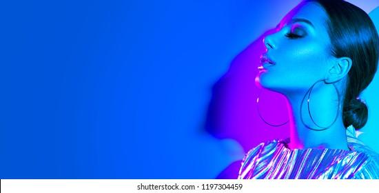 Hoher Fashion Model Girl in bunten, leuchtenden Neonuv-Leuchten posieren im Studio, Portrait von schönen Frauen, trendig leuchtende metallische Make-up, silberne Accessoires Ohrringe. Lebhafter Neonschminken. Weitwinkel