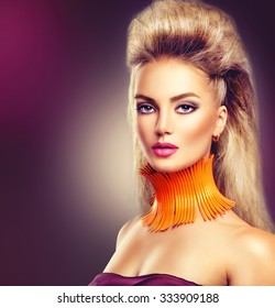 High Fashion Model Girl with Mohawk hairstyle and vivid make up. Beauty woman with glamour updo hair style