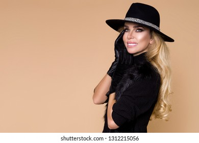 High fashion Model girl portrait isolated on beige background. Beauty stylish blonde woman posing in fashionable clothes in studio. Casual style, beauty accessories.Hat and gloves elegant woman