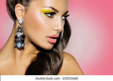 High Fashion Model Girl Portrait over Pink Background. Creative Make up. Yellow Eyeshadow, Ponytail Hairstyle, Trendy Earrings. Perfect Skin