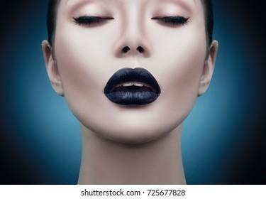 High Fashion Model Girl Portrait with Trendy gothic Black Make up, dark portrait. Halloween Vampire Woman with black matte lips over deep blue background. model girl face with black lipstick makeup.